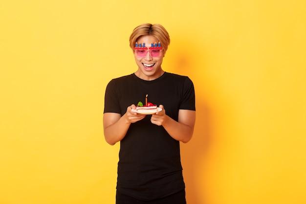 Возбужденный красивый азиатский парень в очках для вечеринок, с надеждой глядя на праздничный торт, празднует день рождения, загадывает желание при зажженной свече, стоит на желтой стене