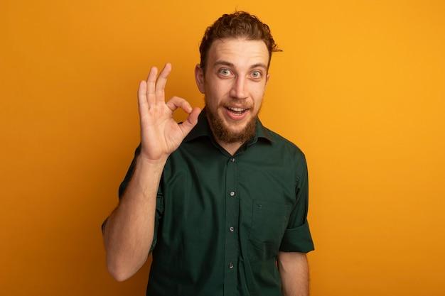 Возбужденный красивый блондин жесты хорошо знаком рукой, изолированной на оранжевой стене