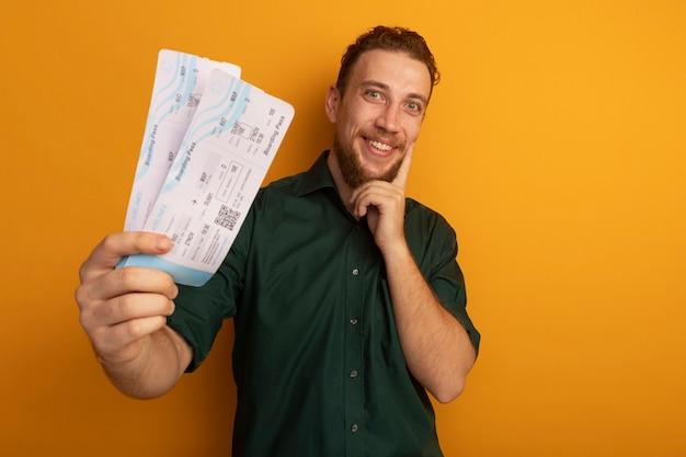 Eccitato bell'uomo biondo tiene i biglietti aerei e mette il dito sul viso isolato sulla parete arancione