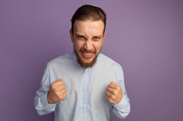 흥분된 잘 생긴 금발의 남자가 보라색 벽에 고립 된 정면을보고 주먹을 유지