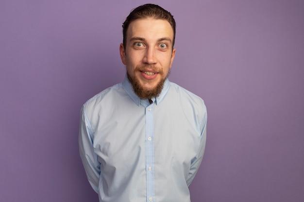 Uomo biondo bello emozionante che esamina fronte isolato sulla parete viola
