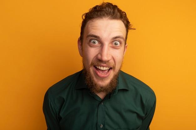 L'uomo biondo bello emozionante esamina la parte anteriore isolata sulla parete arancione