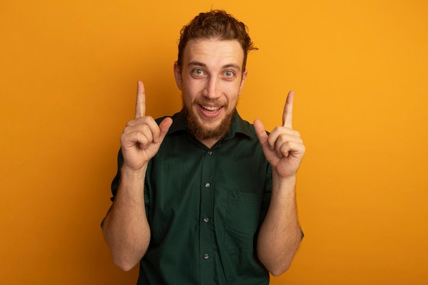 흥분된 잘 생긴 금발의 남자는 오렌지 벽에 고립 된 두 손으로 포인트