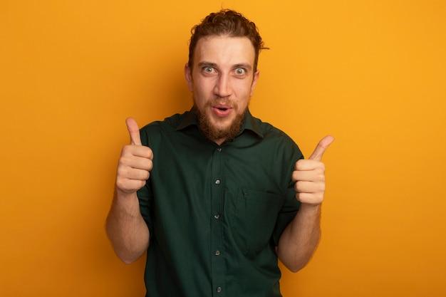 오렌지 벽에 고립 된 두 손으로 흥분된 잘 생긴 금발 남자 엄지 손가락