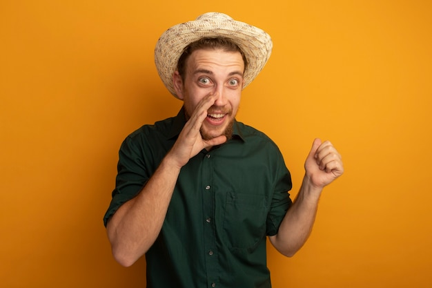 ビーチ帽子をかぶった興奮したハンサムなブロンドの男は、口の近くに手を握り、オレンジ色の壁に拳を隔離し続けます