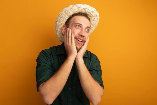 ビーチ帽子をかぶった興奮したハンサムなブロンドの男は顔に手を置き、オレンジ色の壁に隔離された側を見て
