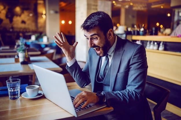 カフェに座っているとラップトップを見てスーツで興奮しているハンサムな白人ひげを生やした実業家。