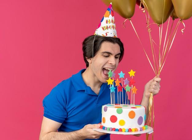 Eccitato bell'uomo caucasico che indossa un berretto di compleanno tiene palloncini di elio e finge di mordere la torta di compleanno