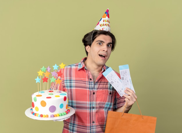 Excited handsome caucasian man wearing birthday cap holds paper shopping bag air tickets and birthday cake