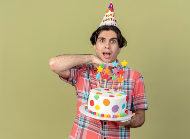Excited handsome caucasian man wearing birthday cap puts hand on chin and holds birthday cake