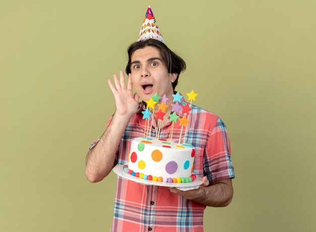 Excited handsome caucasian man wearing birthday cap stands with raised hand and holds birthday cake