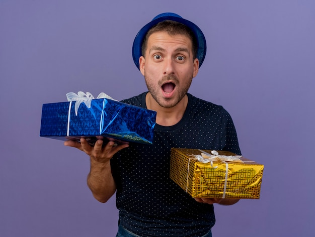 Excited handsome caucasian man wearing blue hat holds gift boxes isolated on purple background with copy space