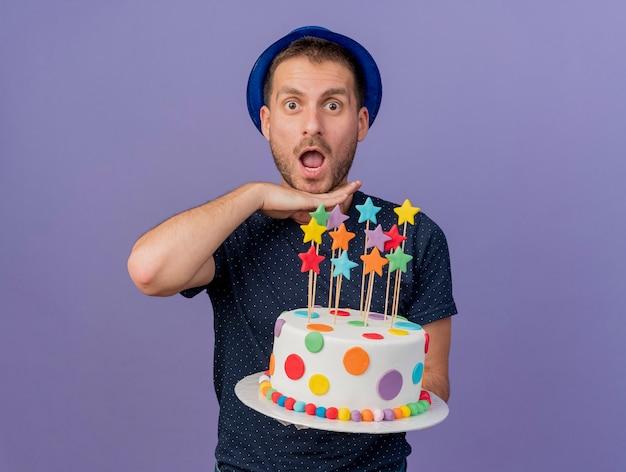 Eccitato uomo caucasico bello che indossa cappello blu tiene la mano sotto il mento e tiene la torta di compleanno isolato su sfondo viola con spazio di copia