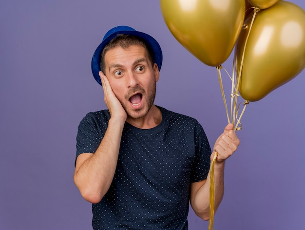 Excited handsome caucasian man wearing blue hat puts hand on face holds helium balloons isolated on purple background with copy space