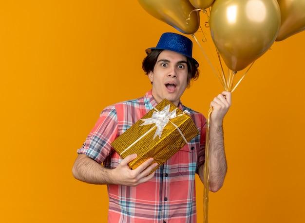 파란색 파티 모자를 쓰고 흥분된 잘 생긴 백인 남자가 헬륨 풍선과 선물 상자를 보유하고 있습니다.