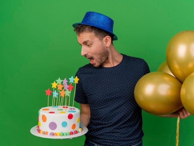파란색 파티 모자를 쓰고 흥분된 잘 생긴 백인 남자는 헬륨 풍선을 보유하고 복사 공간이 녹색 배경에 고립 된 생일 케이크를 본다