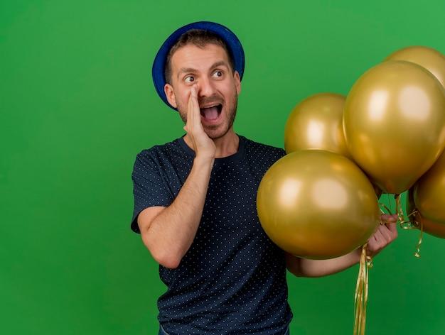 青いパーティーハットを身に着けている興奮したハンサムな白人男性は、ヘリウム気球を保持し、コピースペースで緑の背景に孤立した誰かを呼び出す側を見て
