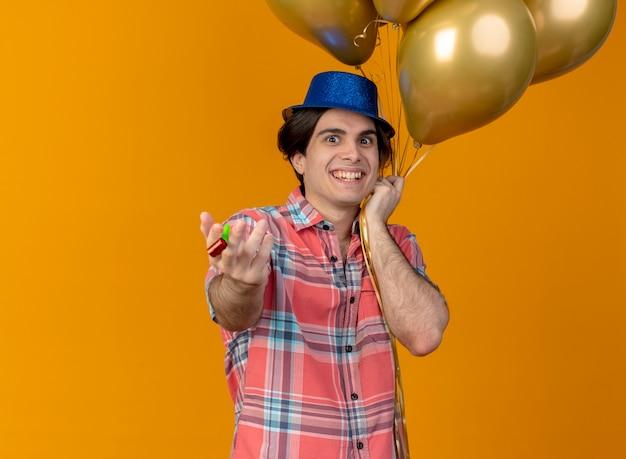 青いパーティー ハットをかぶった興奮したハンサムな白人男性が、ヘリウム風船とパーティー ホイッスルを持っている