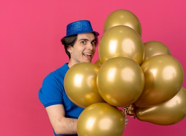 Eccitato bell'uomo caucasico che indossa un cappello da festa blu tiene palloncini di elio