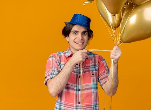 青いパーティー ハットをかぶった興奮したハンサムな白人男性がヘリウム風船を持っている