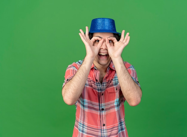 青いパーティー ハットをかぶった興奮したハンサムな白人男性が指を通してカメラを見る