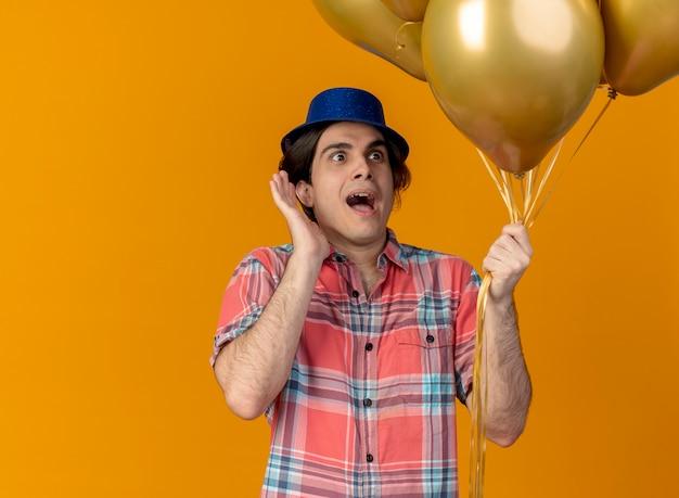 青いパーティー ハットをかぶった興奮したハンサムな白人男性が、ヘリウム風船を持った手を上げて立っています。