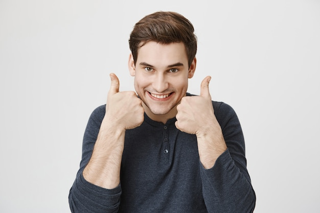 Uomo bello e allegro emozionante che mostra il pollice in su in approvazione