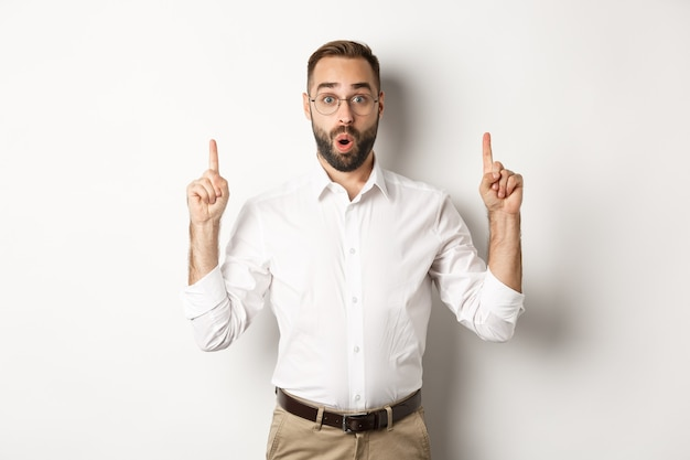 Excited handsome guy in glasses pointing fingers up, showing information banner, standing over white background. copy space