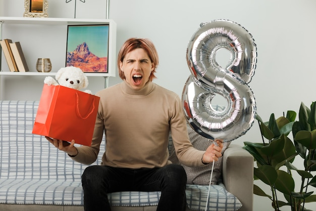 Excited handsome guy on happy women day holding number eight balloon with gift bag sitting on sofa in living room