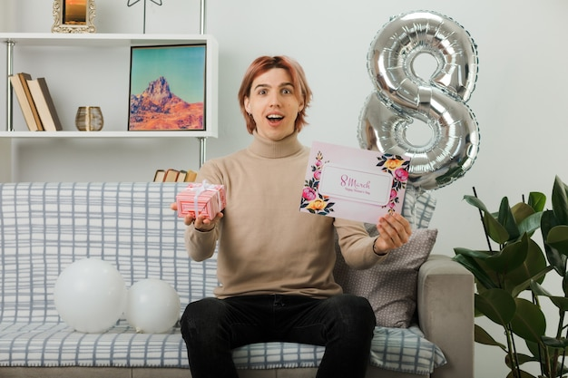 Excited handsome guy on happy women day holding present with greeting card, sitting on sofa in living room