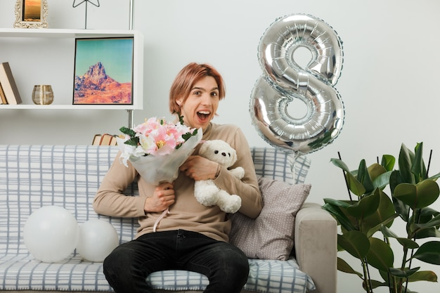행복한 여성의 날 거실 소파에 앉아 있는 테디베어와 함께 꽃다발을 들고 있는 흥분된 잘생긴 남자