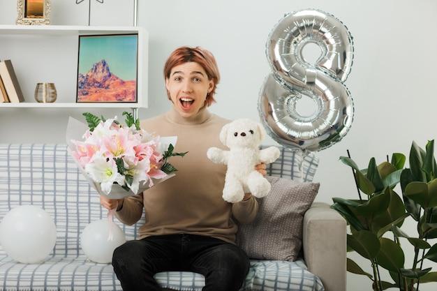 リビングルームのソファに座っているテディベアと花束を持って幸せな女性の日に興奮したハンサムな男