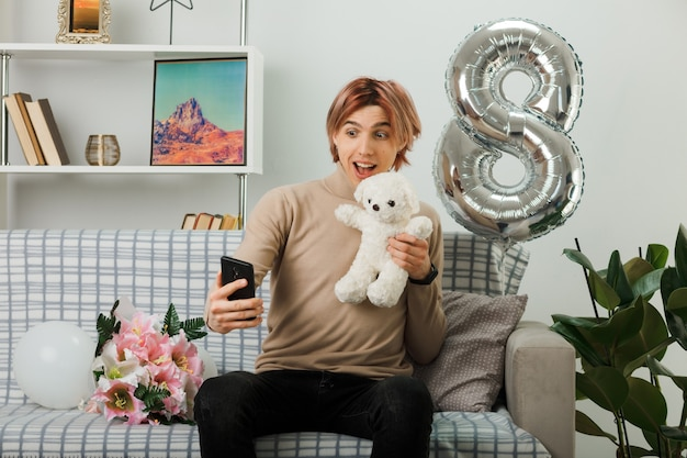 행복한 여성의 날에 흥분한 잘생긴 남자가 거실 소파에 앉아 손에 전화기를 들고 있는 테디베어를 들고 있다