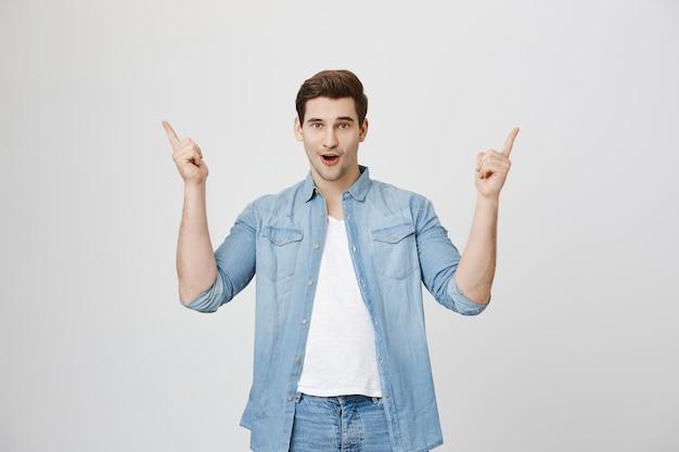 興奮したハンサムな男が指を上に向け、広告を表示