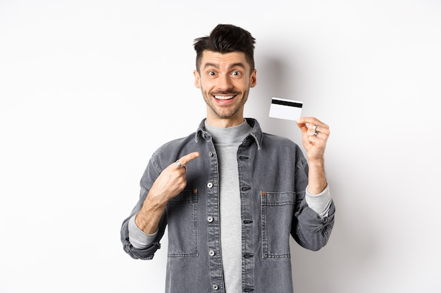 Excited handsome guy with moustache pointing finger at plastic credit card, smiling pleased, recommend good deal, standing on white background.