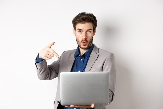 놀란 얼굴로 노트북 화면을 가리키며 여기를 보라고 요청하는 흥분된 잘 생긴 남자
