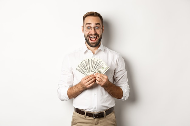 Excited handsome man holding money, rejoicing of winning cash prize, standing over white background.
