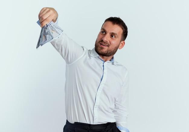 興奮したハンサムな男は、白い壁に隔離されたお金を保持し、見ています