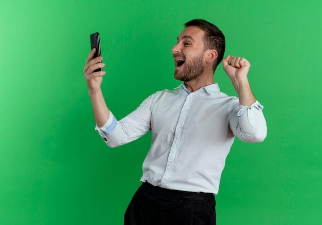 興奮したハンサムな男が保持し、電話を見て緑の壁に隔離された拳を上げる