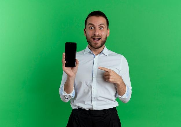 興奮したハンサムな男は、緑の壁に隔離された電話を保持し、指さします