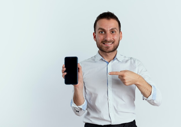 興奮したハンサムな男は、白い壁に隔離された電話を保持し、指さします