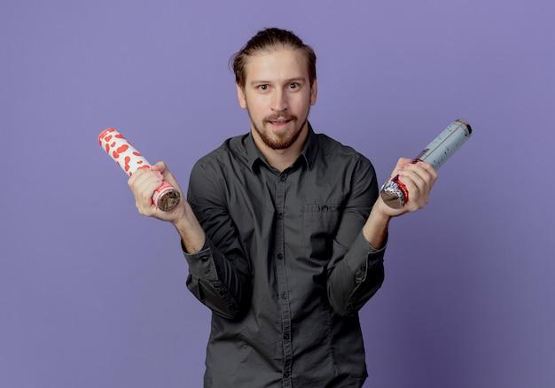 興奮したハンサムな男は、紫色の壁に孤立して見える紙吹雪の大砲を保持します