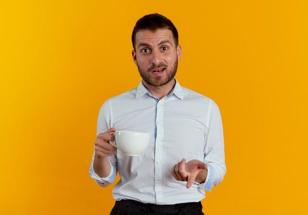 興奮したハンサムな男は、オレンジ色の壁に分離されたカップとポイントを保持します。
