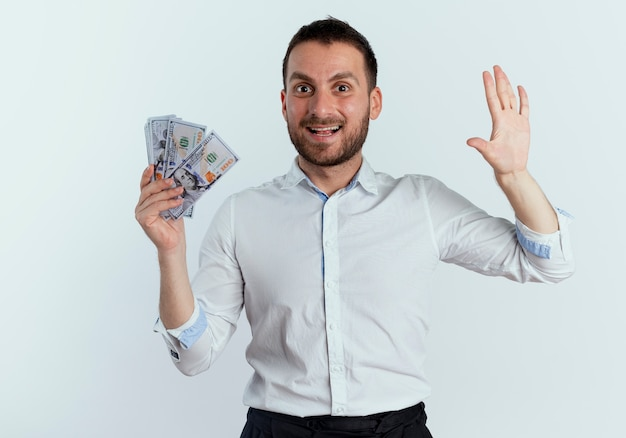 Excited handsome man holds money and raises hand up isolated on white wall