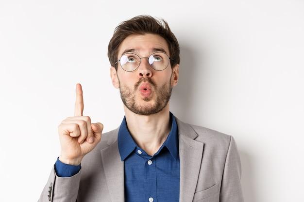 Возбужденный красивый мужчина в очках и деловом костюме, смотрит вверх и, указывая на верхнюю рекламу, восклицает вау с изумленным выражением лица на белом фоне.
