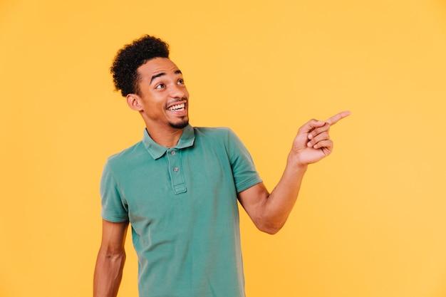 최신 유행 복장 가리키는 손가락에 잘 생긴 남자를 흥분. 녹색 티셔츠에 멋진 웃는 아프리카 남자의 실내 샷.