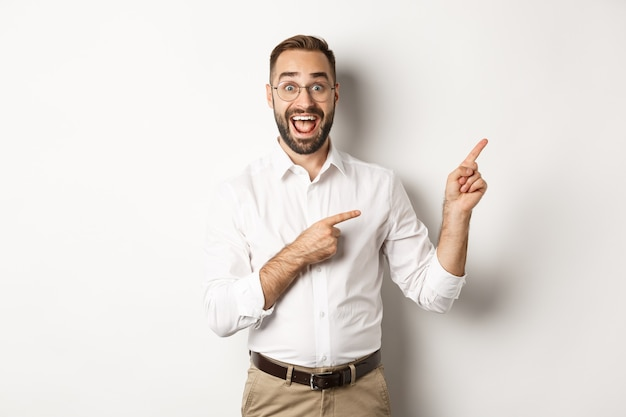 Excited handsome man pointing fingers at upper right corner, showing logo, standing over white background.