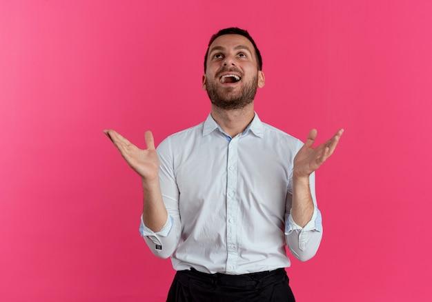 흥분된 잘 생긴 남자가 분홍색 벽에 고립 된 찾고 손을 올립니다