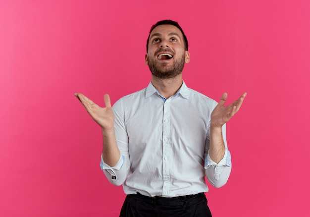 Uomo bello eccitato solleva le mani alzando lo sguardo isolato sulla parete rosa