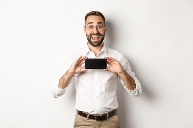 Взволнованный красавец показывает экран мобильного телефона, выглядит удивленно, стоя